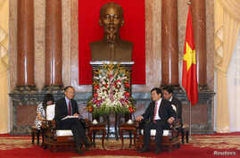 World Bank President Jim Young Kim (front L) and Vietnam's President Truong Tan Sang (front R) meet in front of a statue of late Vietnamese revolutionary leader Ho Chi Minh at the Presidential Palace in Hanoi, July 17, 2014.