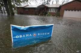A campaign sign rises above floodwaters as rain continues falling in Norfolk, VA.