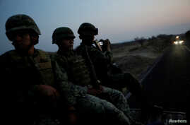 Soldiers sit atop a military vehicle as they arrive for an operation to destroy a poppy field in the municipality of Coyuca de Catalan, Mexico, April 18, 2017.