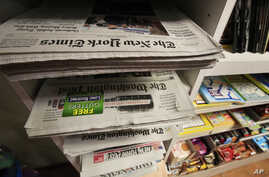 FILE - Newspapers for sale are displayed in a rack at a Washington magazine and newspaper stand, June 11, 2018.