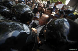 Mam Sonando (C), owner of a local independent radio station, is blocked by police officers during a demonstration in central Phnom Penh, March 31, 2014.