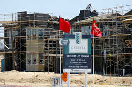 FILE -  Construction of single family homes by Pardee Homes is seen in San Diego, California, June 22, 2016. Construction likely saw a hiring boost in January thanks to warmer weather. The Labor Department will release its monthly report Friday.