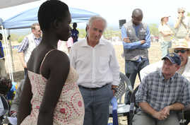 U.S Senators Bob Corker, center, and Chris Coons, right, speak with a South Sudanese refugee during a group discussion at the Bidi Bidi refugee settlement in northern Uganda, April 14, 2017.