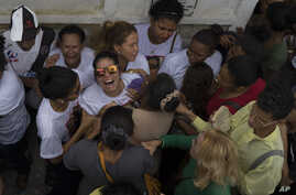 Vilma Carmo Lace, wearing sunglasses, expresses her grief during the burial of her sister Bruna Lace de Freitas, who was killed two days earlier by a stray bullet when she was inside her home, in Rio de Janeiro, Brazil, Friday, Oct. 28, 2016.