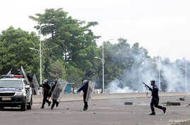 Congolese policemen run to their vehicle during a clash with opposition activists participating in a march to press President Joseph Kabila to step down in the Democratic Republic of Congo's capital Kinshasa, Sept. 19, 2016.