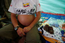 Revolutionary Armed Forces of Colombia's Tatiana, 36 and six months pregnant, sits next to gifts for the baby at a camp where the FARC will ratify a peace deal with the Colombian government, near El Diamante in Yari Plains, Colombia, Sept. 17, 2016.