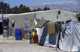 Syrian refugee children stand next to their family tents at a Syrian refugee camp in the town of Bar Elias, in Lebanon's Bekaa Valley, April 23, 2018.