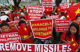Demonstrators display placards during a rally at the Chinese Consulate to protest Beijing's militarization of disputed islands in the South China Sea, in Manila, Philippines, Feb. 25, 2016.
