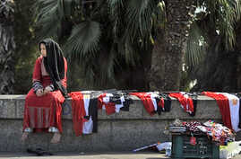 "A young woman sells Egyptian flags in central Cairo. Young activists who spearheaded Egypt's pro-democracy revolution called for a ""no"" vote in next weekend's referendum on constitutional reform, March 14, 2011"