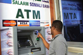 Somali man uses first-ever ATM cash withdrawal machine in the country, Mogadishu, on Oct. 7, 2014.
