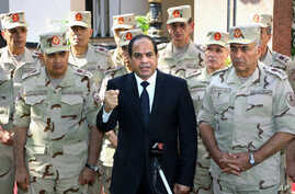 In this photo provided by Egypt's state news agency MENA, Egyptian President Abdel-Fattah el-Sissi speaks in front of the state-run TV ahead of a military funeral for troops killed in an assault in the Sinai Peninsula, as he stands with army commande...