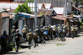 FILE - Philippine Marines advance their positions as more soldiers reinforce to fight the Maute group in Marawi City in southern Philippines May 29, 2017.