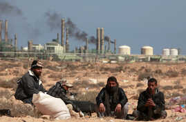 Anti-Gaddafi rebels sit on the ground near an oil facility in Ras Lanuf, March 10, 2011. The rebel leadership said on Thursday that the oil port of Ras Lanuf in eastern Libya is under heavy bombardment.