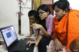 A young school girl in Dhaka, Bangladesh, is teaching her mother how to use Facebook. (S. M. Ashfaque for VOA)