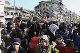 FILE -- This Wednesday, Jan. 14, 2015 file photo, hundreds of Syrians mingle amid rubble before going out of town to buy food and other essential materials as they wait in line at a military checkpoint in the town of Beit Sahm, south of the capital,
