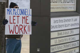 Furloughed EPA worker Jeff Herrema holds a sign outside the offices of U.S. Senator Mitch McConnell, in Park Hills, Kentucky, Jan 22, 2019.