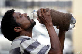 An Indian drinks water from a bottle on a hot summer day in Allahabad, India, Sunday, May 31, 2015.