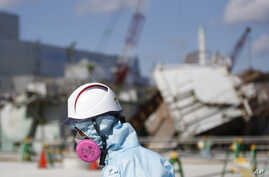 FILE - A Tokyo Electric Power Co. (TEPCO) employee, wearing a protective suit and a mask, walks in front of the No. 1 reactor building at the tsunami-crippled Fukushima Dai-ichi nuclear power plant in Okuma, Fukushima Prefecture, northeastern Japan,