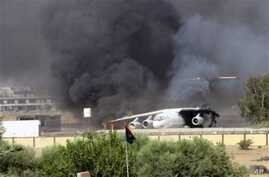 In this Saturday, July 26, 2014 frame grab from video obtained from a freelance journalist traveling with the Misarata brigade, shows an airplane on the tarmac of the airport belching black smoke into the air during fighting between the Islamist Misa