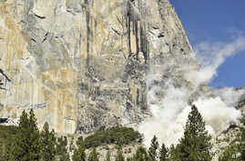 A cloud of dust rises at the base of El Capitan after a major rock fall in Yosemite National Park, Calif., Sept. 27, 2107. An official says a British climber was killed an another injured in Wednesday's rock fall.\