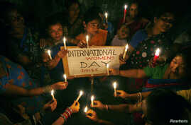 FILE - Sex workers hold candles during a rally to mark International Women's Day inside a brothel in the northeastern Indian city of Siliguri, March 8, 2008.