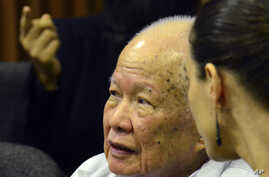 In this photo released by the Extraordinary Chambers in the Courts of Cambodia, Khieu Samphan, left, former Khmer Rouge head of state, sits in the court room during a hearing at the U.N.-backed war crimes tribunal, in Phnom Penh, Cambodia, Oct. 17, 2