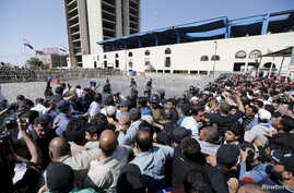 Supporters of prominent Iraqi Shi'ite cleric Muqtada al-Sadr try to remove a barbed wire fence as they break the checkpoint on the bridge leading to Baghdad's heavily fortified Green Zone in Iraq, March 18, 2016.