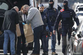 Police look at bags of evidence material during a search in the Brussels borough of Schaerbeek following Tuesday's bombings in Brussels, Belgium, March 25, 2016.