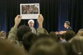 A protester holds up photos of Iranian dissidents under house as Iran's President Hassan Rouhani speaks in New York on Wednesday, Sept. 24, 2014.