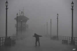 A man struggles against gusty wind and heavy rain as he walks along a pier in Huntington Beach, Calif., Feb. 17, 2017. A major Pacific storm has unleashed downpours and fierce gusts on Southern California, triggering flash flood warnings and other pr