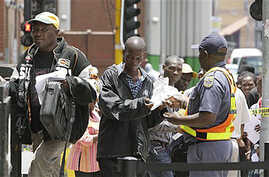 Zimbabweans pass a police cordon to submit their application forms in a last-minute bid to have their status in South Africa legalized, outside the Immigration offices in Johannesburg, Dec 31, 2010