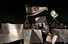 Israelis hold signs and flags as they protest the cease-fire in the southern Israeli city of Kiryat Malachi, Wednesday, Nov. 21, 2012.