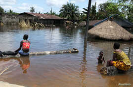 People sit in front of a submerged building in the Patani community in Nigeria's Delta state, which was hit by severe floods in the past few weeks, October 15, 2012.