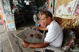 A Palestinian man reads a newspaper outside his store in Gaza City September 19, 2016.