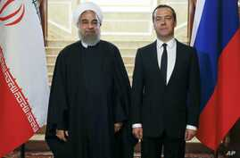 Russian Prime Minister Dmitry Medvedev, right, and Iranian President Hassan Rouhani pose for a photo during their meeting in the Gorky residence outside Moscow, Russia, March 27, 2017.