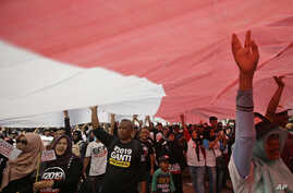 """People wear T-shirts that read """"Replace the President in 2019"""" stand under a large national flag during a rally in Jakarta, Indonesia, May 6, 2018."""