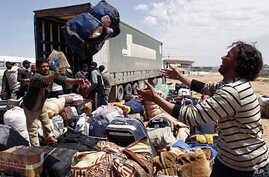 An evacuee reaches out for his luggage at the Libyan Red Crescent camp in Benghazi Apr 16 2011