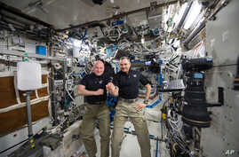 FILE - One-year mission crew members Scott Kelly of NASA, left, and Mikhail Kornienko of Roscosmos their 300th consecutive day in space, Jan. 21, 2016. The pair landed March 1 after spending a total of 340 days in space.