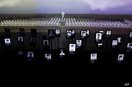 File - Photographs of Argentine soldiers who died in the Falklands War between Argentina and Great Britain are displayed inside Malvinas Museum in Buenos Aires, Argentina, Sept. 18, 2015. The two countries reached a deal, Dec. 20, 2016, to identify t