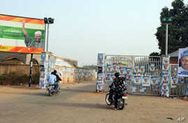 Members of the Party Loyalists drive their motocycles outside the entrance of a park in front of posters  featuring  Nigeria's opposition leader Mohammadu Buhari (R) and Nigeria's President Goodluck Jonathan and his Vice President Namadi Sambo (L)  i