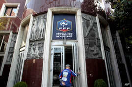 FILE - In this May 6, 2011 file photo, a man enters the French soccer federation headquarters in Paris. Swiss authorities say evidence has been seized in a search made Tuesday March 8, 2016 at the French soccer federation headquarters for their crimi