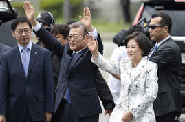 South Korea's new President Moon Jae-in waves to neighborhoods and supporters with his wife Kim Jung-sook upon their arrival outside the presidential Blue House in Seoul, South Korea, May 10, 2017.