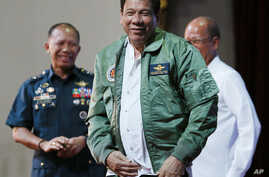 "Philippine President Rodrigo Duterte, center, smiles as he is presented with a pilot's jacket during his ""Talk with the Airmen"" on the anniversary of the 250th Presidential Airlift Wing Tuesday, Sept. 13, 2016 at the Philippine Air Force headquarters"