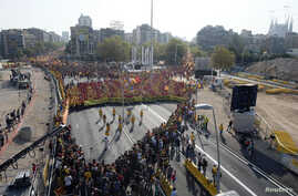 "People form a ""V"" for ""vote"" in red and yellow, colors of the Catalan flag, to mark ""Diada,"" central Barcelona, Sept. 11, 2014."