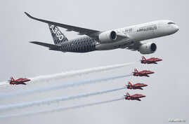 FILE - An Airbus A350 aircraft flies in formation with Britain's Red Arrows flying display team at the Farnborough International Airshow in Farnborough, Britain, July 15, 2016.