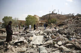 People gather as they inspect Youth and Sports Ministry's building destroyed by Saudi-led airstrikes in Sana'a, Yemen, Jan. 17, 2016. (