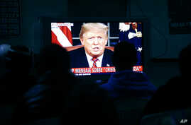 FILE - Migrants mainly from Mexico and Central America watch from a border migrant shelter in Tijuana, Mexico, as U.S. President Donald Trump gives a prime-time address about border security Jan. 8, 2019.