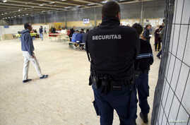 Securitas security guards stand in a Swiss federal refugee center in Thun, Switzerland, March 22, 2016.