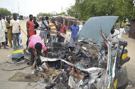 FILE- People gather at the scene of a suicide car bombed explosion in Maiduguri, Nigeria,  Oct. 12, 2016. Radical Islamic militants from Boko Haram are increasingly forcing children to carry out bombings.