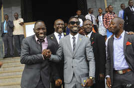 FILE - Ugandan pop star Kyagulanyi Ssentamu, better known as Bobi Wine, center, leaves shortly after being sworn in as a member of parliament in Kampala, Uganda, July 11, 2017. The 36-year-old urges his countrymen to stand up against what he calls a